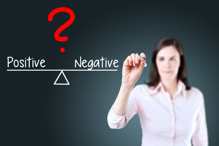introspective: Young business woman writing on balance positive and negative Compare bar. Blue background. Stock Photo