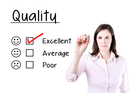 Hand putting the check mark with red marker on excellent quality evaluation form.