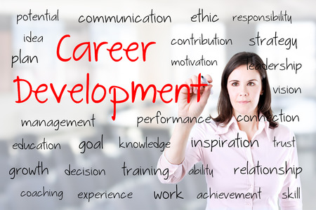 career development: Young business woman writing career development concept. Office background. Stock Photo