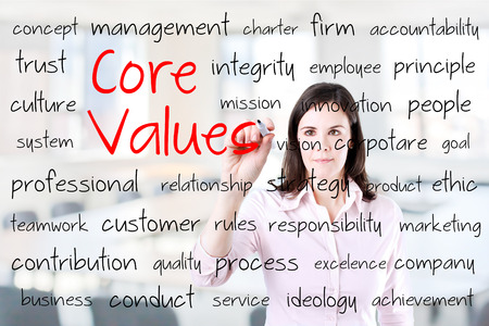 core strategy: Young business woman writing concept of core values. Office background.
