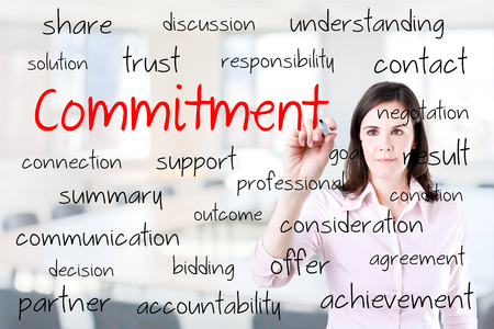 obligate: Young business woman writing Commitment concept. Office background.