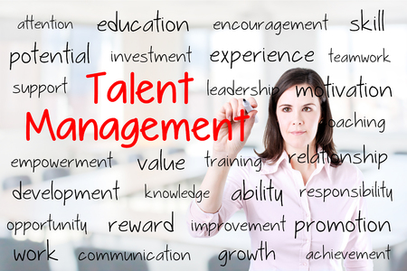 talent management: Business woman writing talent management concept. Office background. Stock Photo