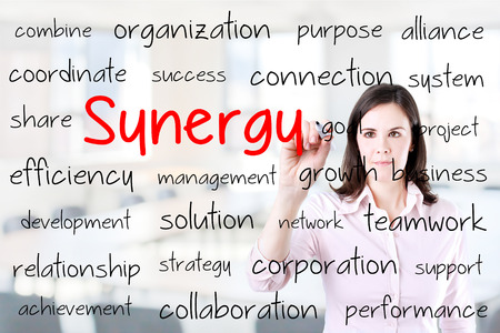 concurrence: Business woman writing synergy concept. Office background.