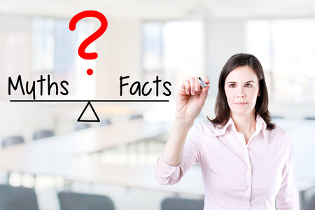 myths: Young business woman writing on myths and facts compare balance bar. Office background.