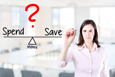 spend: Young business woman writing spend compare and save on balance bar. Office background. Stock Photo