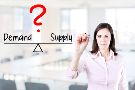 correlate: Young business woman writing on demand and supply balance compare bar. Office background.