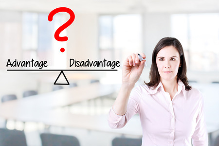disadvantage: Young business woman writing Advantage and Disadvantage compare on balance bar. Office background. Stock Photo