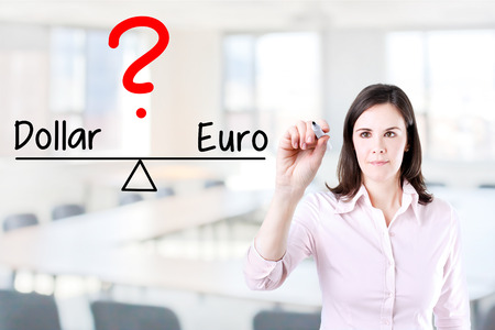 valorization: Young business woman writing dollar and euro compare on balance bar. Office background. Stock Photo