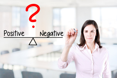 conclusive: Young business woman writing on balance positive and negative Compare bar. Office background.