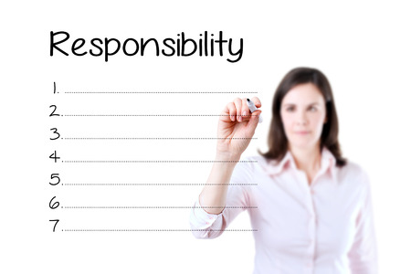 educator: Business woman writing in blank Responsibility list. Isolated on white. Stock Photo