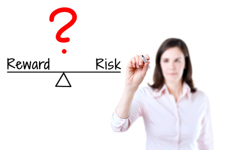 equivalent: Young business woman writing question compare with risk to reward on balance bar. Isolated on white background. Stock Photo