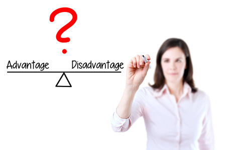 disadvantage: Young business woman writing Advantage and Disadvantage compare on balance bar. Isolated on white background. Stock Photo