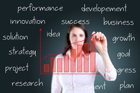 performance improvement: Young business woman writing business growth graph with related text. Stock Photo