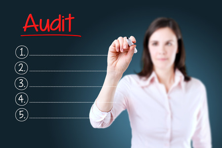 audits: Business woman writing blank Audit list. Blue background. Stock Photo