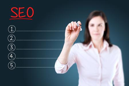 Business woman writing blank SEO (search engine optimization) list. Blue background.
