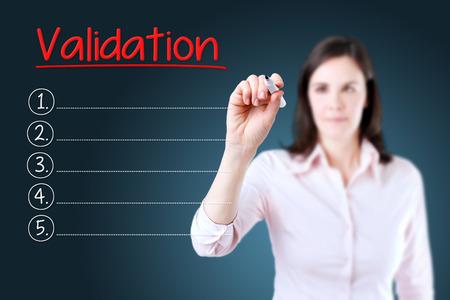 validation: Business woman writing blank Validation list. Blue background.
