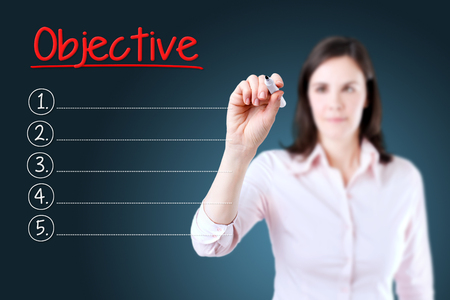 audits: Business woman writing blank Objective list. Blue background. Stock Photo