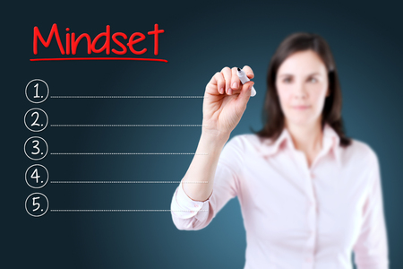 mindset: Business woman writing blank Mindset list. Blue background.