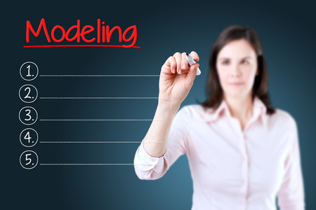 modeling: Business woman writing blank Modeling list. Blue background.