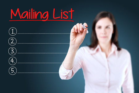 mailing: Business woman writing blank Mailing Lists list. Blue background. Stock Photo