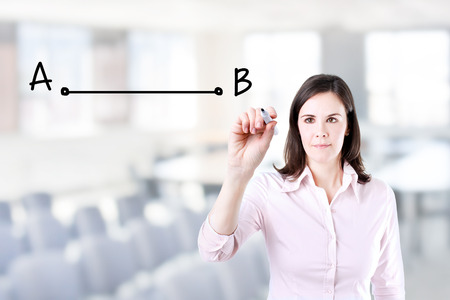shortest: Business woman drawing the shortest way to move from point A to point B. Office background.