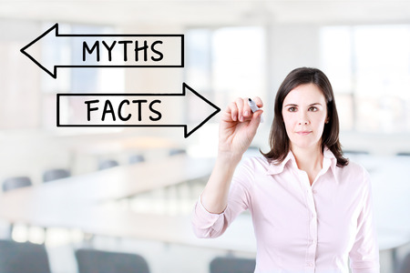 myths: Businesswoman drawing of Myths or Facts concept on the virtual screen. Office background. Stock Photo