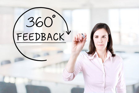 Businesswoman drawing a 360 degrees Feedback concept on the virtual screen. Office background. Standard-Bild