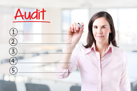 Business woman writing blank Audit list. Office background.