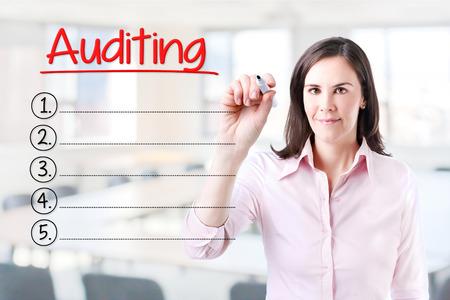 validez: Mujer de negocios por escrito la lista de Auditoría en blanco. Fondo de la oficina.