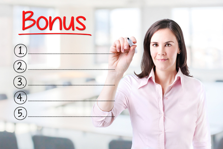 compensated: Business woman writing blank Bonus list. Office background.