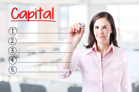 ownership and control: Capital Business woman writing blank list. Office background. Stock Photo