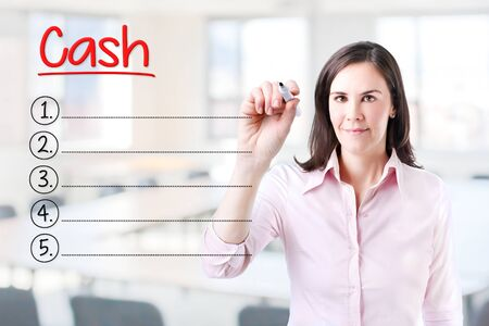cash flow statement: Business woman writing blank list Cash. Office background. Stock Photo
