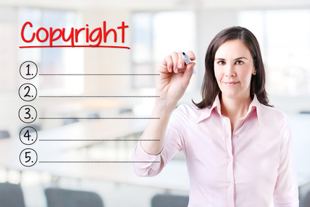 authorship: Copyright Business woman writing blank list. Office background. Stock Photo