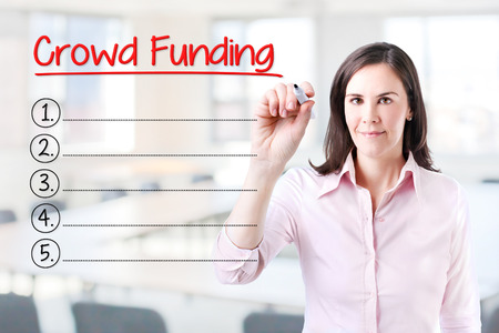initiator: Business woman writing blank Crowd Funding list. Office background. Stock Photo