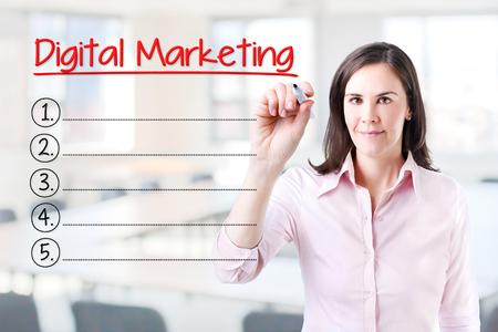 marketers: Business woman writing blank Digital Marketing list. Office background.