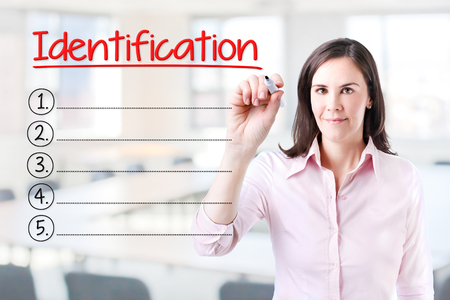 control fraud: Business woman writing blank Identification list. Office background. Stock Photo