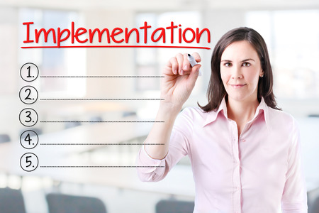 implementation: Business woman writing blank Implementation list. Office background.