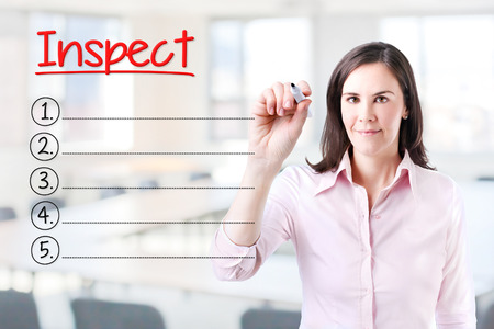 audits: Business woman writing blank Inspect list. Office background. Stock Photo