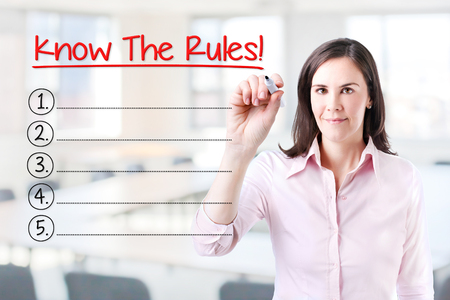 Business woman writing blank Know The Rules! List. Office background.