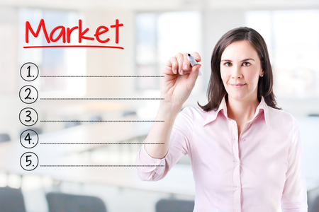 decoding: Business woman writing blank Market list. Office background.