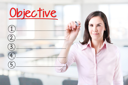 audits: Business woman writing blank Objective list. Office background. Stock Photo