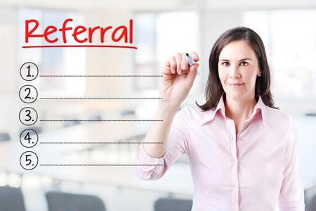 referidos: Mujer de negocios por escrito la lista de referencias en blanco. Fondo de la oficina. Foto de archivo