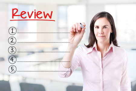 reassessment: Business woman writing blank Review list. Office background. Stock Photo