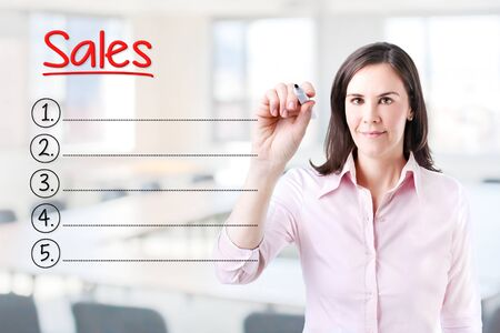 relationsip: Business woman writing blank Sales list. Office background.