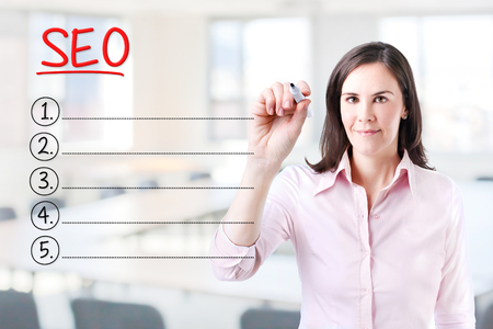 meta analysis: Business woman writing blank SEO (search engine optimization) list. Office background.