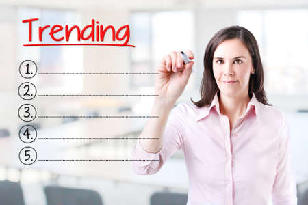 Business woman writing blank Trending list. Office background.