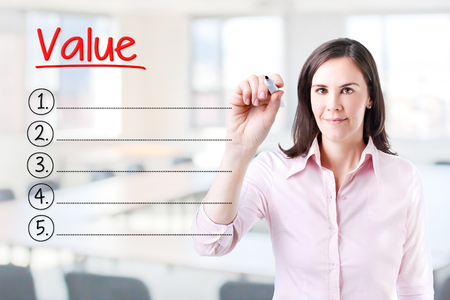 Business woman writing blank Value list. Office background.