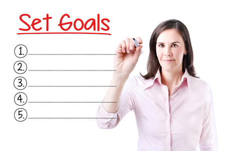 personal decisions: Business woman writing blank Set Goals list. Isolated on white.