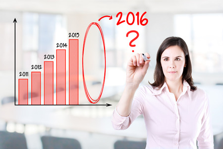 year increase: Businesswoman writing question about 2016 on graph. Office background. Stock Photo
