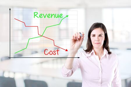 Businesswoman writing graph comparing revenue and cost. Office background. Standard-Bild